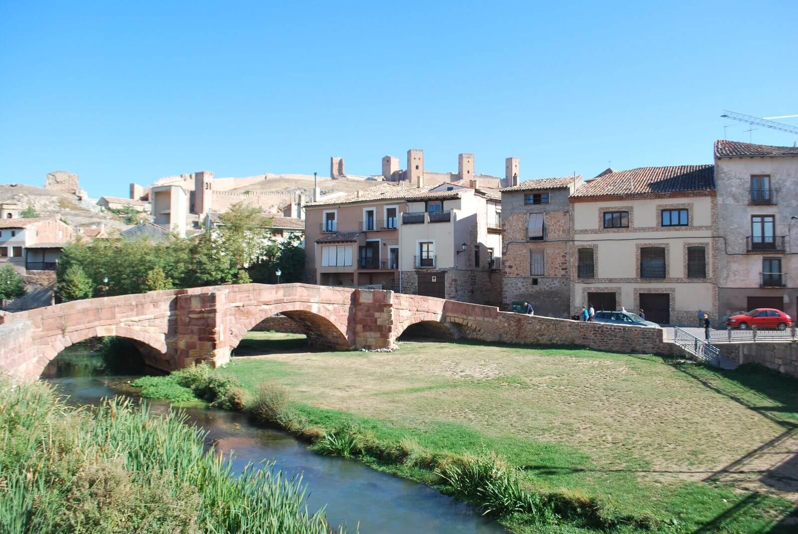 Vuelta a España 2021 Stary most na rzece Gallo, XIII w., w tle średniowieczny alcazar w Molina de Aragón, Hiszpania